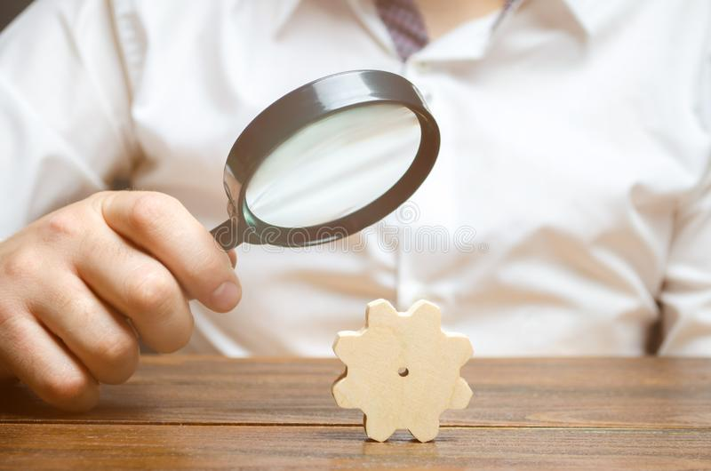 Businessman examines a wooden gear through a magnifying glass. study and analysis of business processes and subjects. royalty free stock photos