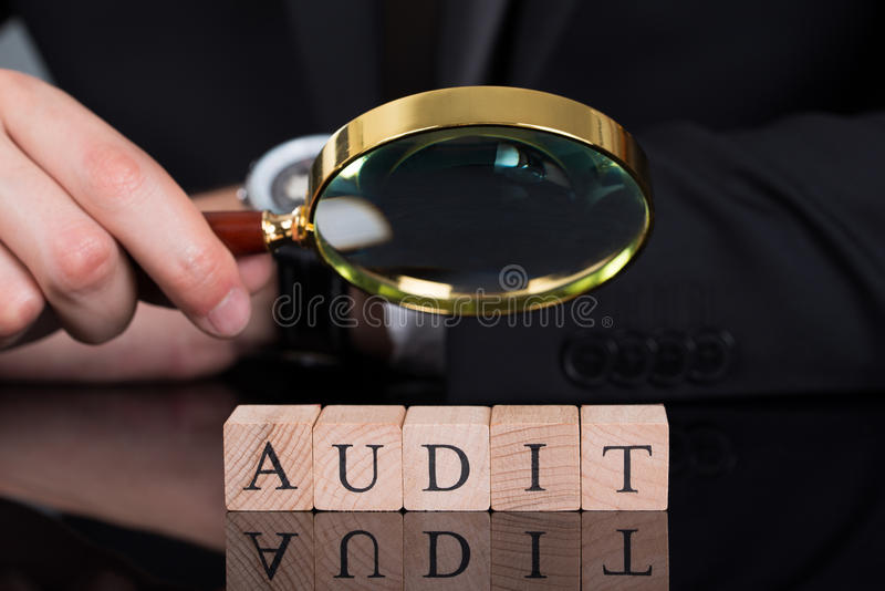 Businessman examining audit blocks through magnifying glass. Midsection of young businessman examining Audit blocks through magnifying glass on desk royalty free stock photos