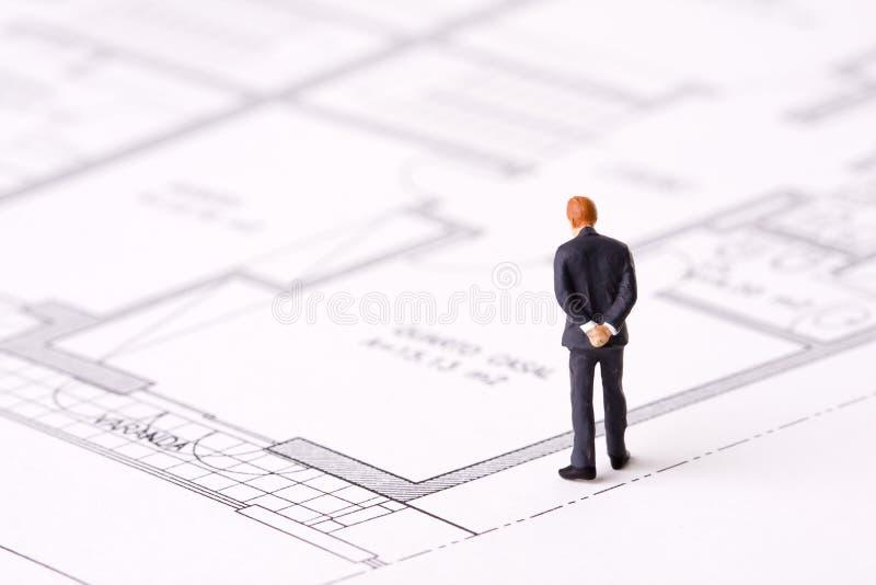 Businessman examining a blueprint stock image