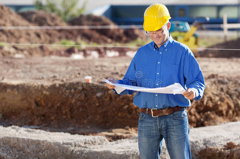 Businessman Examining Blueprint At Construction Site royalty free stock images