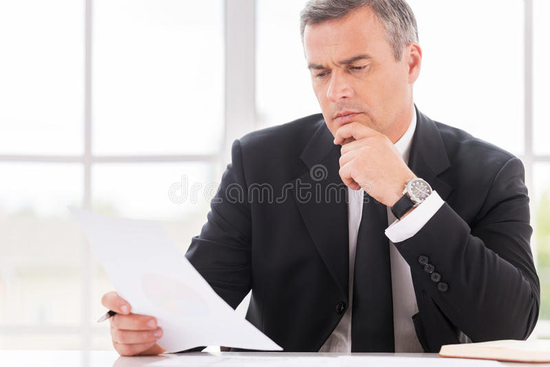 Businessman examining contract. Thoughtful mature man in formalwear holding hand on chin while examining document and sitting at working place royalty free stock photos