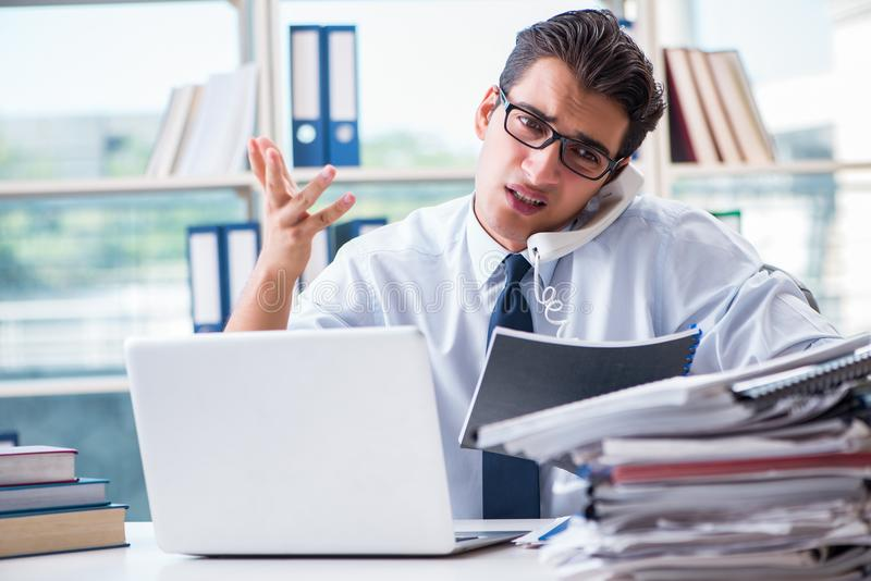 The businessman with excessive work paperwork working in office royalty free stock image