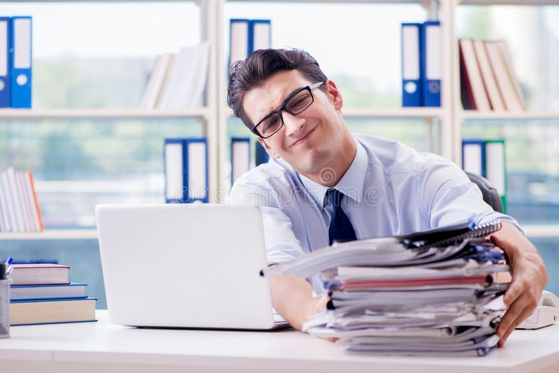 The businessman with excessive work paperwork working in office stock photos
