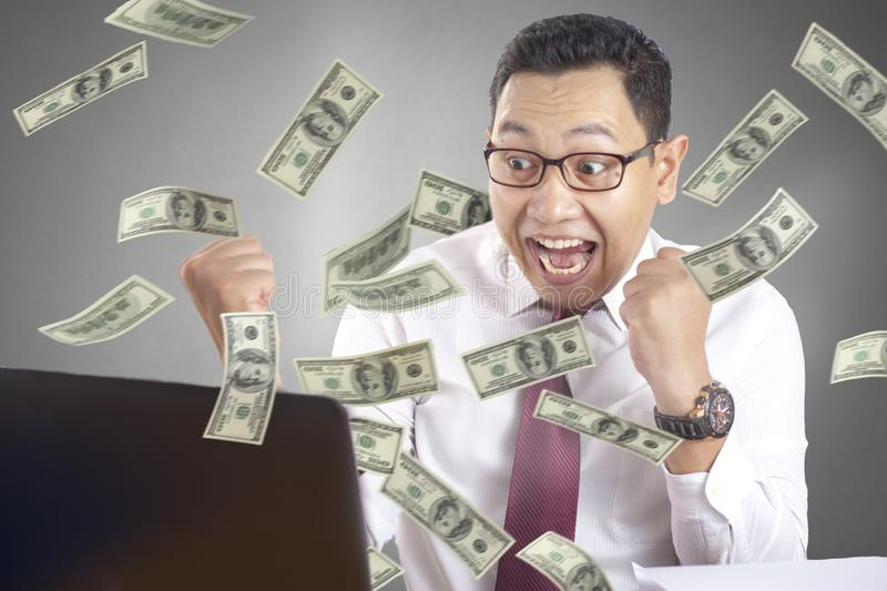 Businessman Excited to See Money From His Laptop. Portrait of young Asian businessman using laptop shows surprised excited facial expression gesture with rain of royalty free stock photography