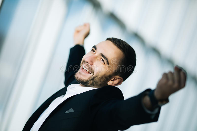 Businessman executive raising fists in excitement in office stock photography