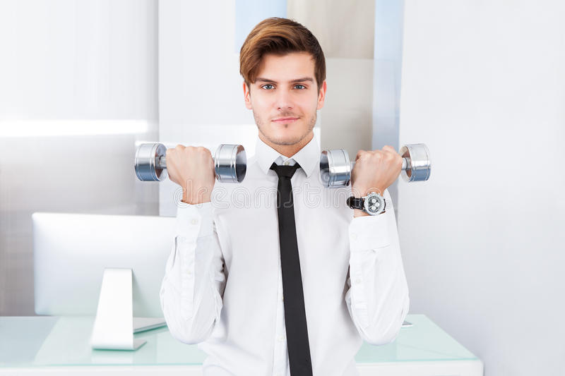 Businessman exercising with dumbbells. Handsome Young Businessman Exercising With Dumbbells At Office royalty free stock photography