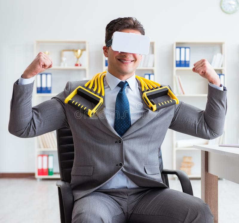 Businessman exercising with elastic expander wearing VR glasses. The businessman exercising with elastic expander wearing vr glasses stock images