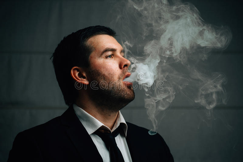 Businessman exhales cigarette smoke. Young successful businessman exhales cigarette smoke white clubs stock image
