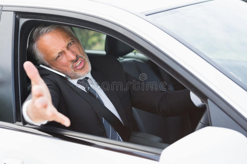 Businessman experiencing road rage. In his car stock photo