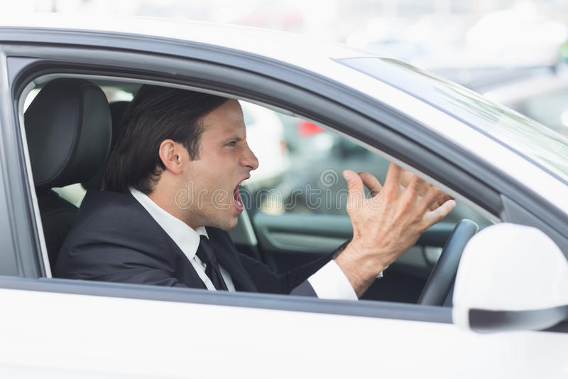 Businessman experiencing road rage. In his car royalty free stock photos