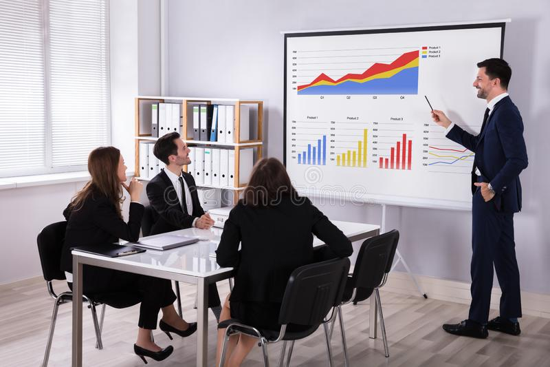Businessman Explaining Graphs To His Colleagues royalty free stock image