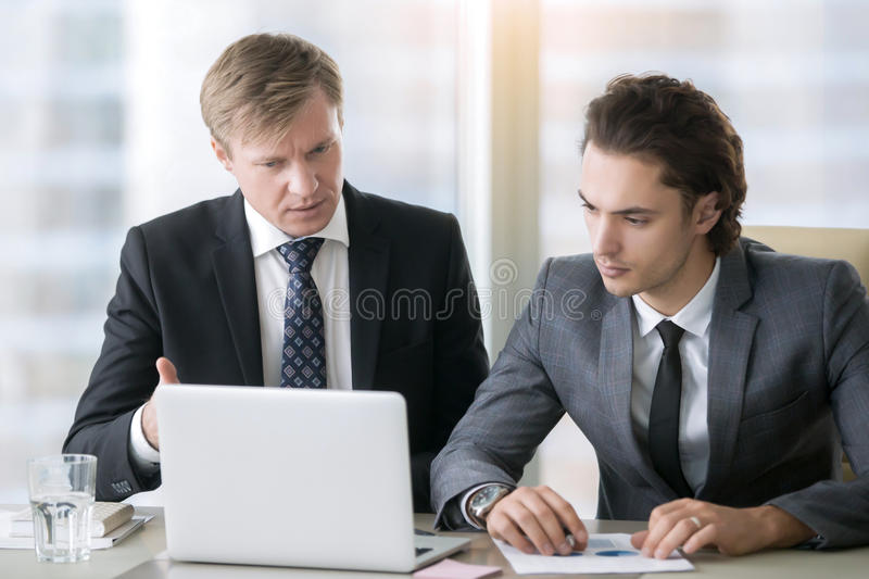 Businessman explaining presentation on laptop screen royalty free stock images