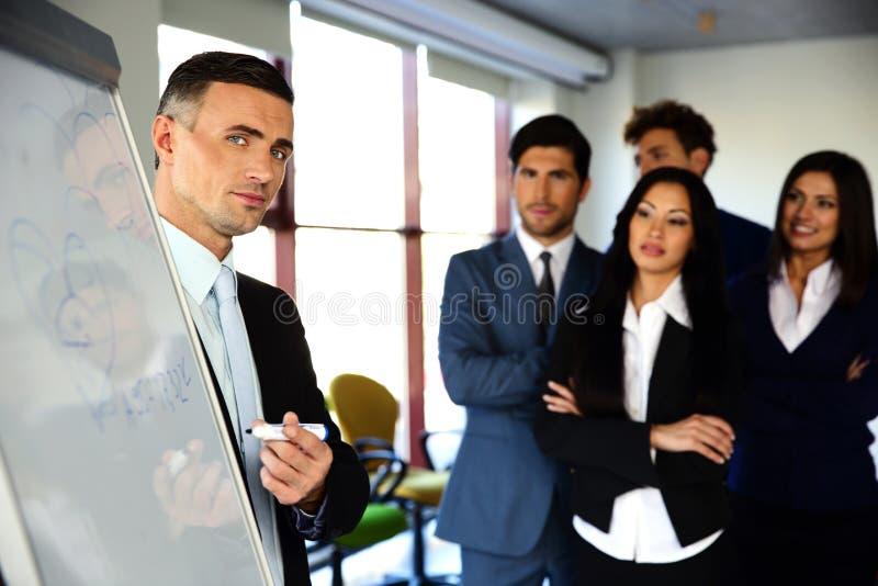 Businessman explaining something on the flipboard royalty free stock image