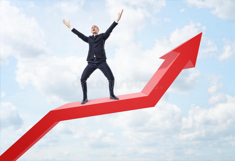 Businessman expressing happy and standing on big red line graph with an upturned arrow. Businessman expressing happy and standing on a big red line graph with an royalty free stock photo