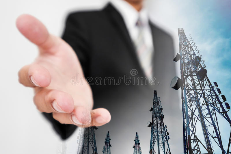 Businessman extending hand, with double exposure Telecommunication towers with TV antennas and satellite dish royalty free stock photo