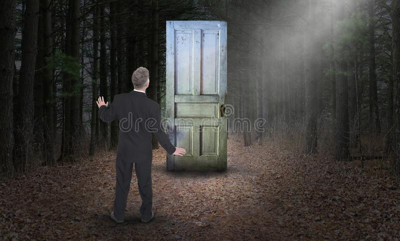 Opportunity, Goals, Risk, Success, Unknown. A businessman faces the unknown, opportunity, goals, risk and success. A man faces a closed door in a surreal woods stock photography
