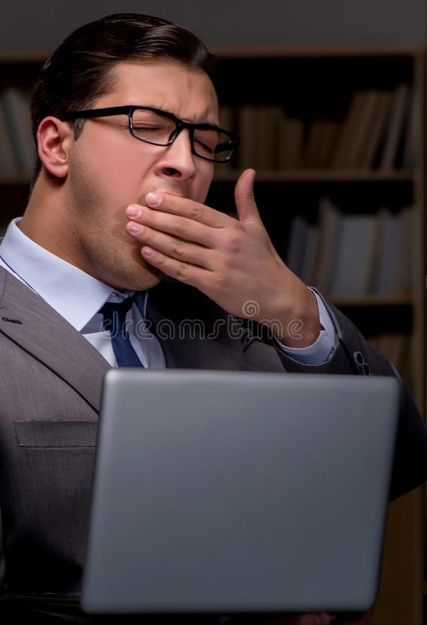 Businessman almost falling asleep working late hours in the offi. Ce royalty free stock photo