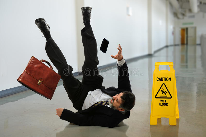 Businessman Falling. Senior businessman falling near caution sign in hallway royalty free stock photo