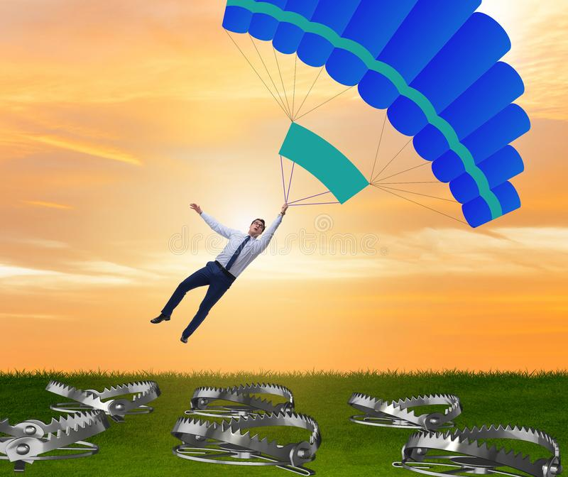 Businessman falling into trap on parachute stock image