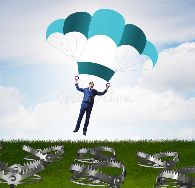 Businessman falling into trap on parachute stock photography