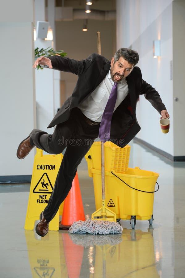 Businessman Falling on Wet Floor stock photo