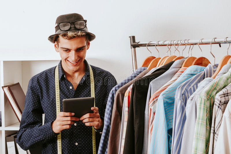 Businessman in fashion with the tablet store. Casual young staff blogger shopper in the textile workshop stock photos