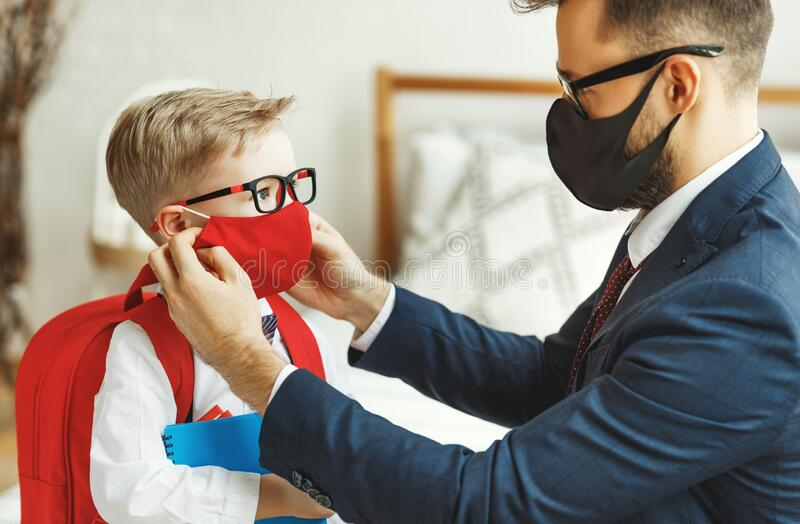 Businessman father accompanies his son to school putting on a mask to protect and prevent coronavirus stock photos