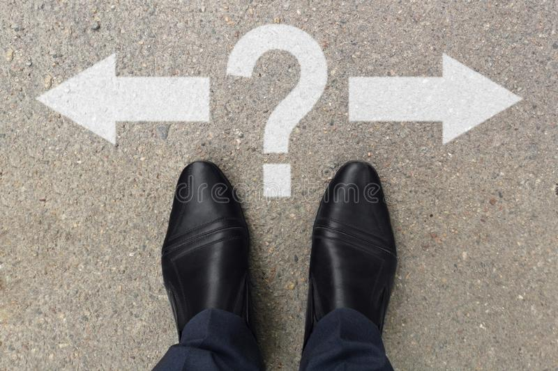 Businessman feet in shoes standing on asphalt road markings with arrows pointing left and right with question mark. Pair of feet stock images