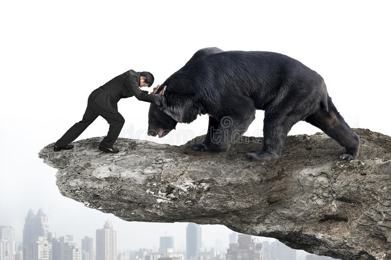 Businessman fighting against black bear on cliff with sky citysc. Ape background stock photos