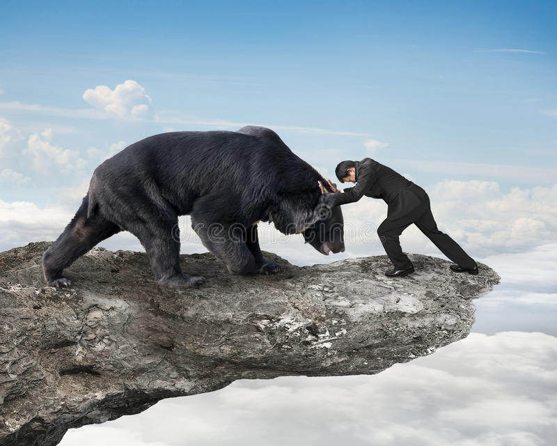Businessman fighting against black bear on cliff with sky clouds. Cape background royalty free stock photography