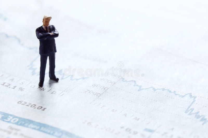 Businessman figure on a stock chart. Conceptual picture of abusinessman figure standing on a stock chart on financial pages from a newspaper stock images