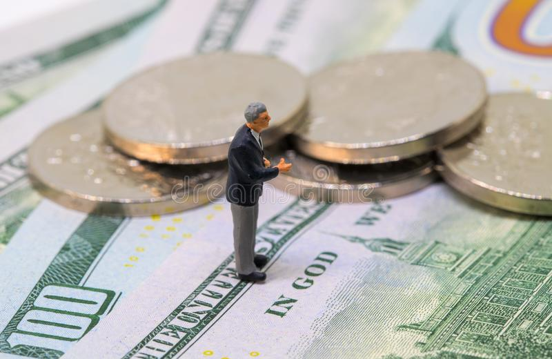 Businessman figurine on dollars and coins. Business man stand on money concept. royalty free stock image