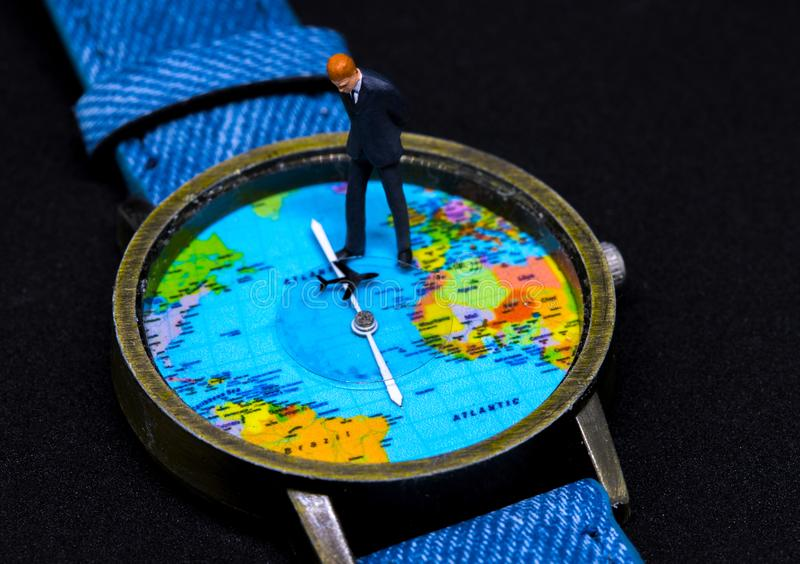 Businessman figurine on watch. World map clock. Worldwide business concept. stock photography