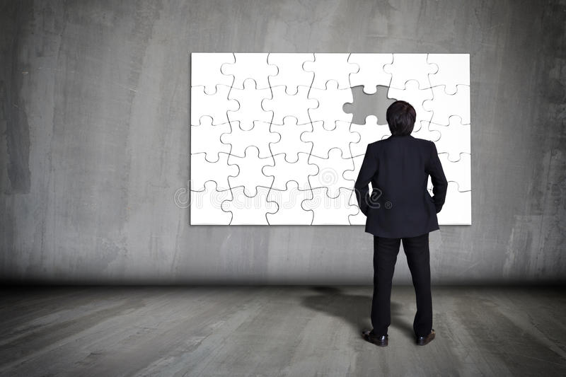 Businessman figuring out puzzle pieces. With piece missing on grey wall, Business concept stock image