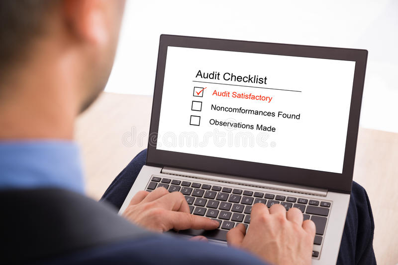 Businessman filling audit checklist form. Close-up Of A Businessman Filling Audit Checklist Form On Laptop royalty free stock photo