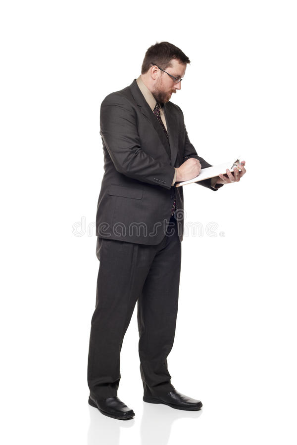 Businessman filling out job application. Isolated full length studio shot of the side view of a businessman writing on a clipboard stock images