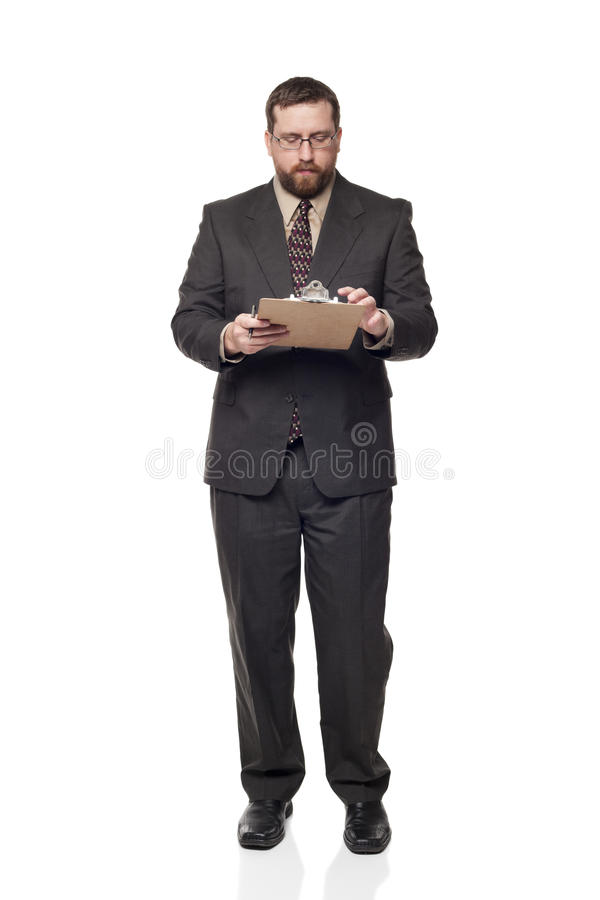 Businessman filling out job application. Isolated full length studio shot of the front view of a businessman writing on a clipboard stock photography