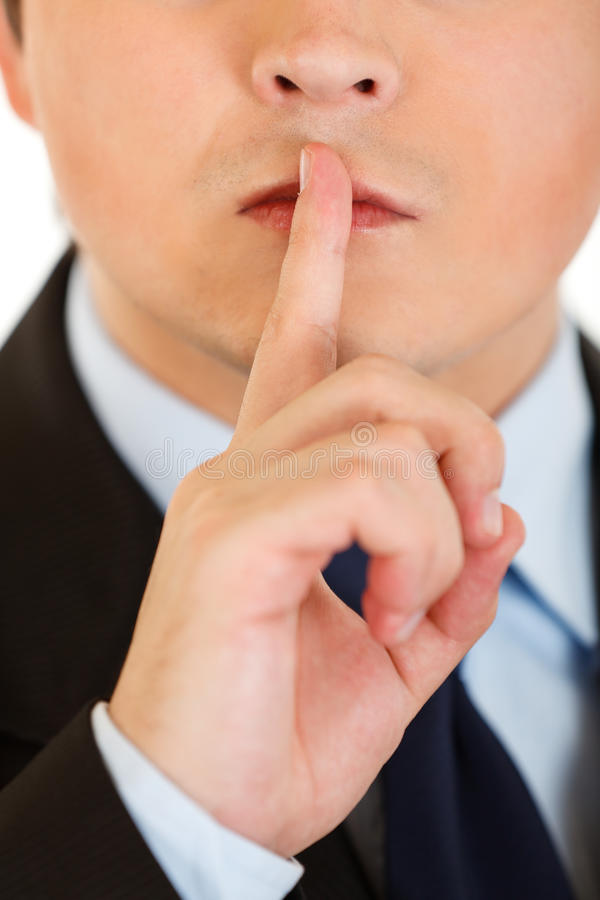 Businessman with finger at mouth. Shh gesture stock photos