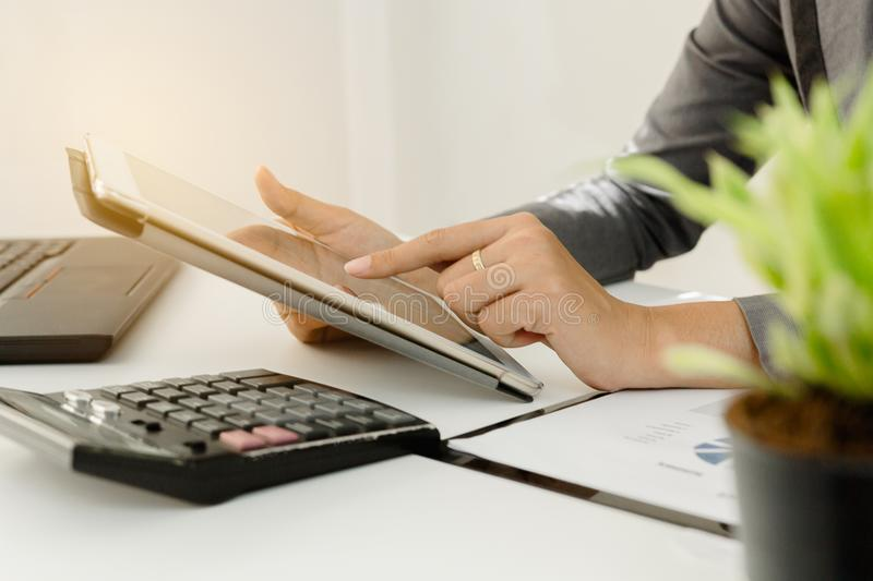 Businessman with finger touching screen of a digital tablet at office on table with document graph data.  stock images