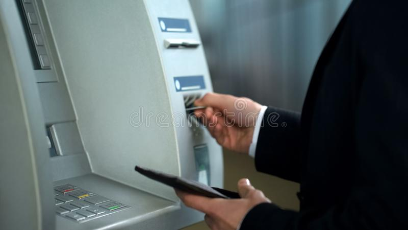 Businessman finishing banking transaction, removing card from ATM, banking. Stock photo stock photography