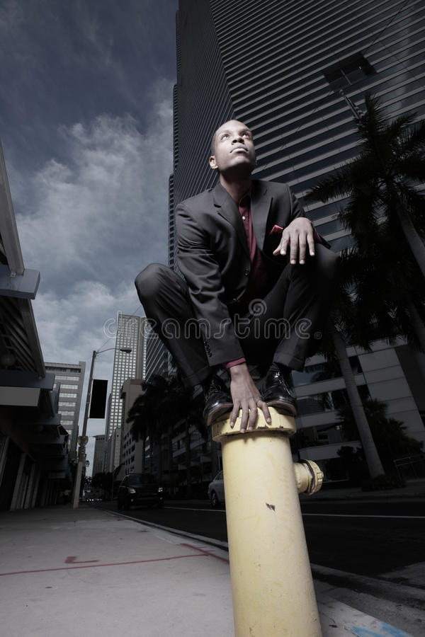 Businessman on a fire hydrant royalty free stock photography