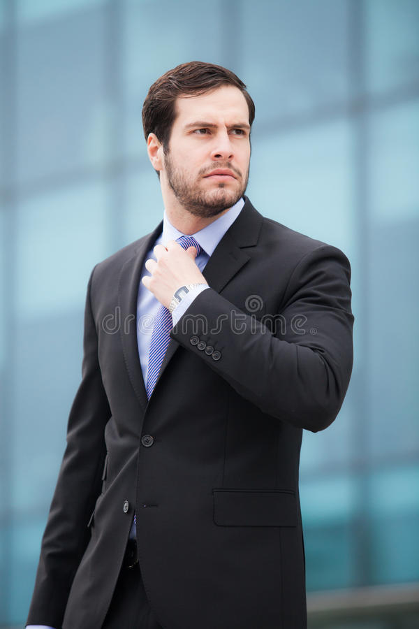Businessman fixing his tie stock images