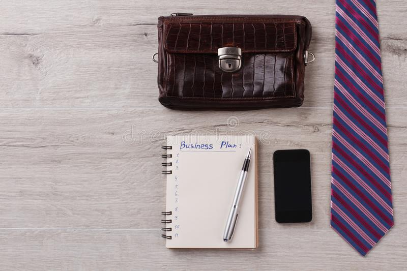 Businessman flatlay on wooden surface. Tie, notepad with pen. Mobile phone and leather wallet. Business concept royalty free stock image