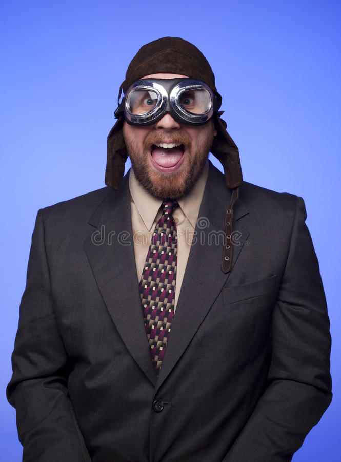 Businessman flight helmet goggles funny expression. A businessman in old fashioned flight helmet and goggles with a silly expression royalty free stock photo