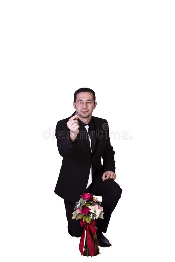 Businessman with Flowers and a Ring Proposing. Isolated Businessman with Flowers Holding an Engagement Ring Down on His Knee Proposing stock photo