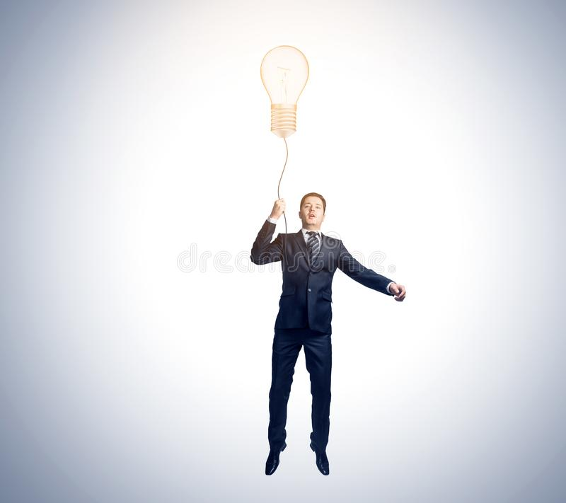 Idea and innovation concept. Businessman flying with abstract glowing lamp balloon. Idea and innovation concept royalty free stock images