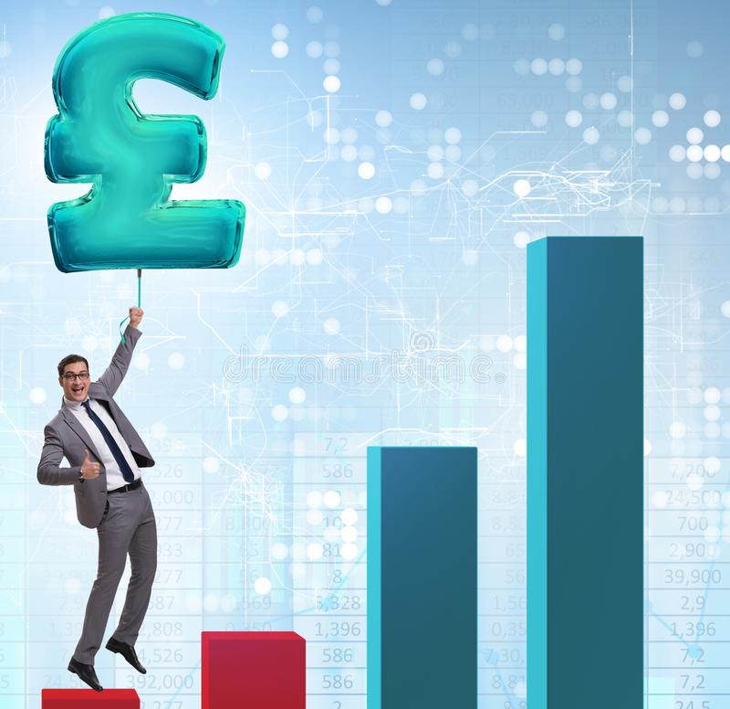 The businessman flying on british pound sign inflatable balloon. Businessman flying on british pound sign inflatable balloon stock photo
