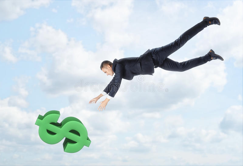The businessman flying down to the big dollar sign with his hands outstreched on the background of the blue sky. royalty free stock photos