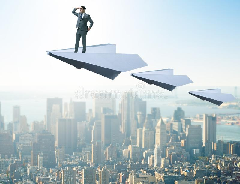 Businessman flying on paper plane in business concept. The businessman flying on paper plane in business concept royalty free stock photos