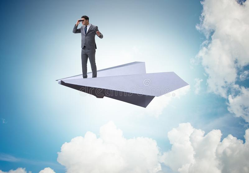Businessman flying on paper plane in business concept. The businessman flying on paper plane in business concept royalty free stock photography